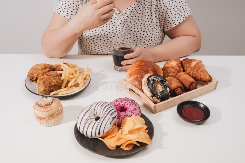 Fêmea Curvy que prepara-se para comer o Hamburger, comendo demais o problema, depressão imagens de stock