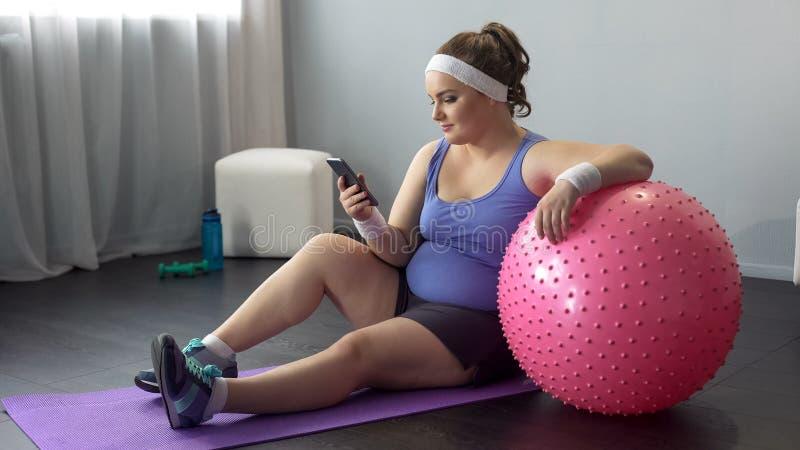 Fêmea Curvy que verifica resultados da maratona em linha do emagrecimento após o exercício home imagens de stock royalty free