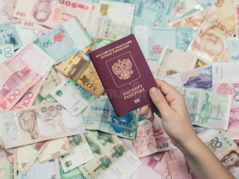 A fêmea dá o russo que o passaporte com embarque passa sobre o fundo do dinheiro de Ásia Conceito do curso e do negócio Controle  imagens de stock royalty free