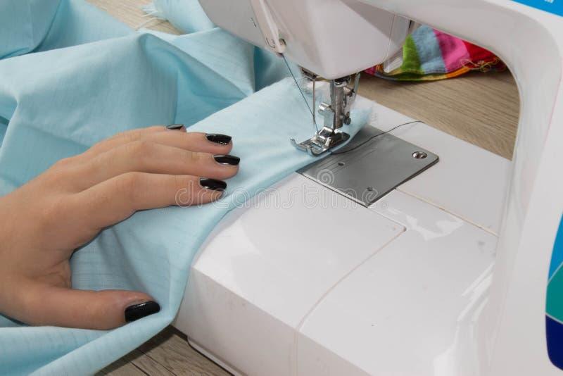 A fêmea da costureira costura a roupa e põe a linha na agulha Local de trabalho do alfaiate povos, bordado e conceito da costura  fotografia de stock