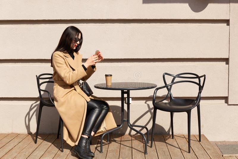 A fêmea de cabelo preta delgada senta-se na tabela fora, tendo o copo da bebida quente, relaxando durante o tempo livre, tomando imagens de stock royalty free