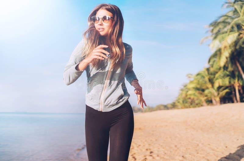 A fêmea de cabelos compridos nova elegante tem a manhã que movimenta-se na praia do beira-mar fotos de stock royalty free