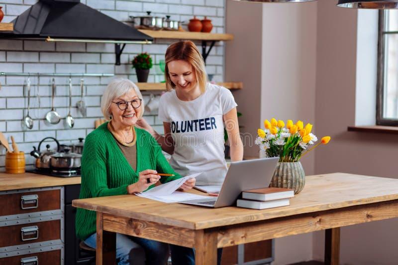 Fêmea de envelhecimento de sorriso e para oferecer-se tendo a conversação sobre o enchimento dos documentos imagem de stock
