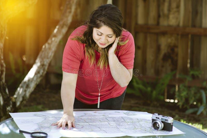A fêmea de Latina revê um mapa para fazer seus planos durante o curso com câmera e lupa imagem de stock