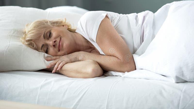Fêmea de meia idade feliz que dorme na cama no colchão ortopédico, resto saudável imagens de stock