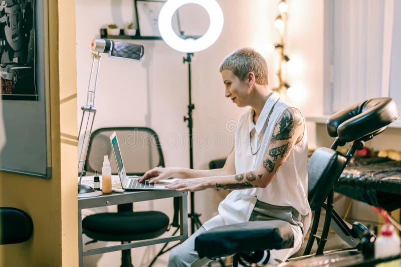 Fêmea de sorriso com o corte de cabelo à rapaz que trabalha com seu portátil fotografia de stock royalty free