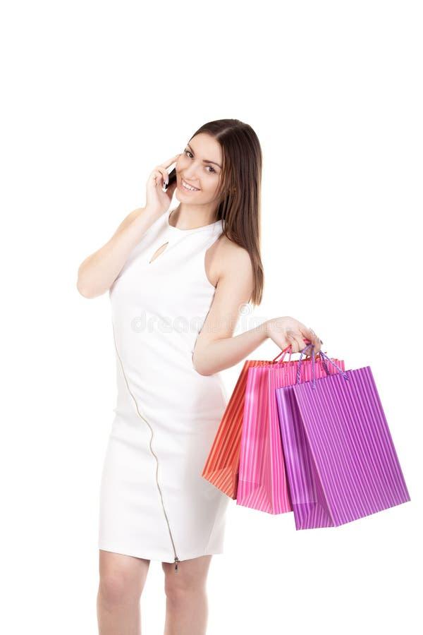 Fêmea de sorriso com sacos de compras coloridos que fala no telefone celular foto de stock