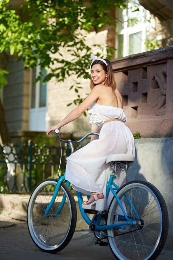 Fêmea de sorriso no dia ensolarado na bicicleta na rua da cidade fotos de stock