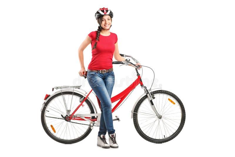 Fêmea de sorriso que levanta ao lado de uma bicicleta imagem de stock royalty free