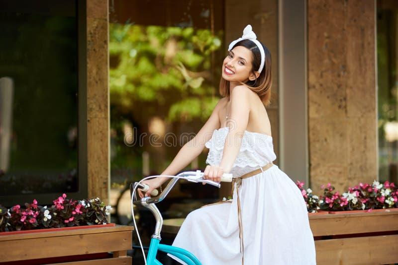 Fêmea de sorriso que monta uma bicicleta perto do café decorado confortável imagem de stock