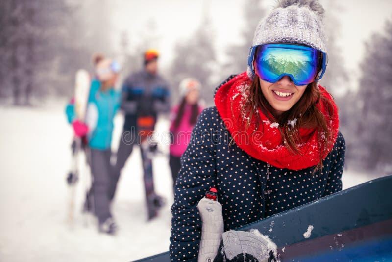 A fêmea desportiva de sorriso guarda o snowboard nas montanhas no inverno imagem de stock royalty free