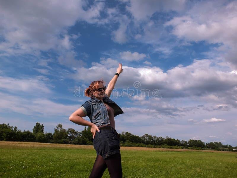 Fêmea 35 do céu azul do verde anos de calças de brim do prado fotos de stock royalty free