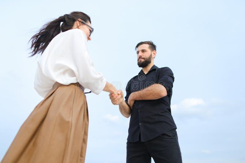 a fêmea do corretor de imóveis e o homem de negócio concordam sobre a casa de compra em imagem de stock