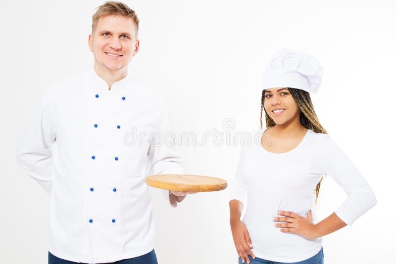 A fêmea do preto do sorriso e os cozinheiros masculinos brancos dos cozinheiros chefe mantêm uma bandeja vazia isolada no fundo b imagens de stock royalty free