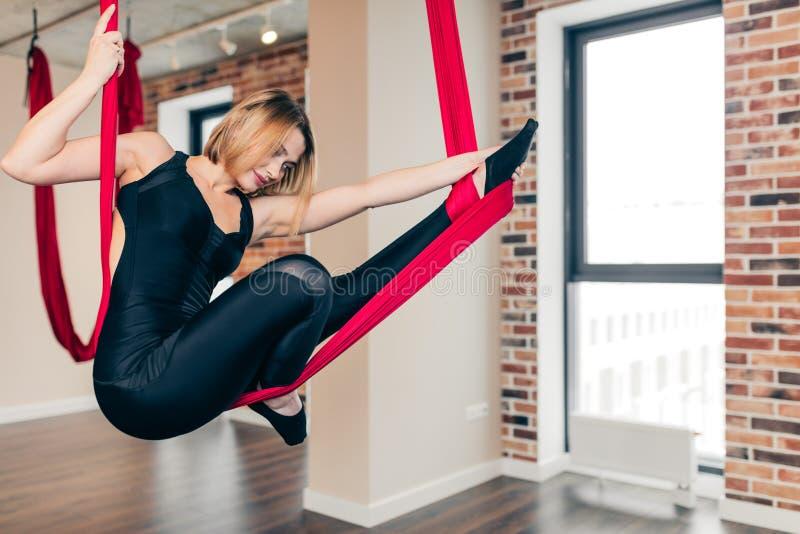 A fêmea do yogini do ajuste diversifica seus exercícios que executam exercícios antigravitantes da ioga imagem de stock royalty free