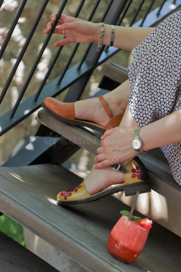 Fêmea em um vestido que senta-se em escadas com a morango fresca no lado imagens de stock royalty free