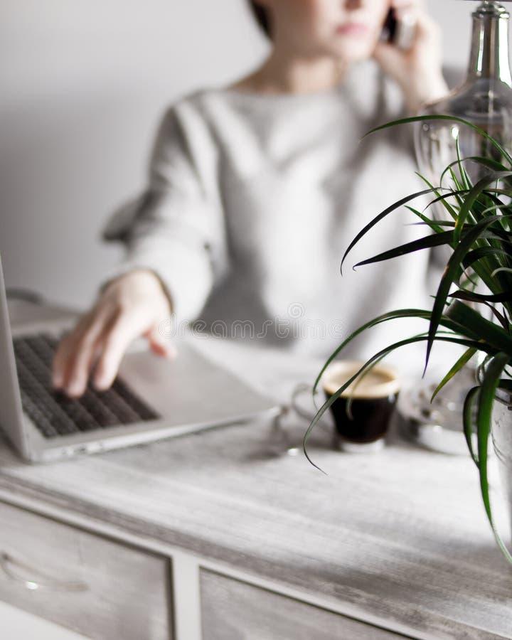 Fêmea em uma camiseta cinzenta que fala no telefone com sua mão em um portátil e em um café na tabela imagens de stock