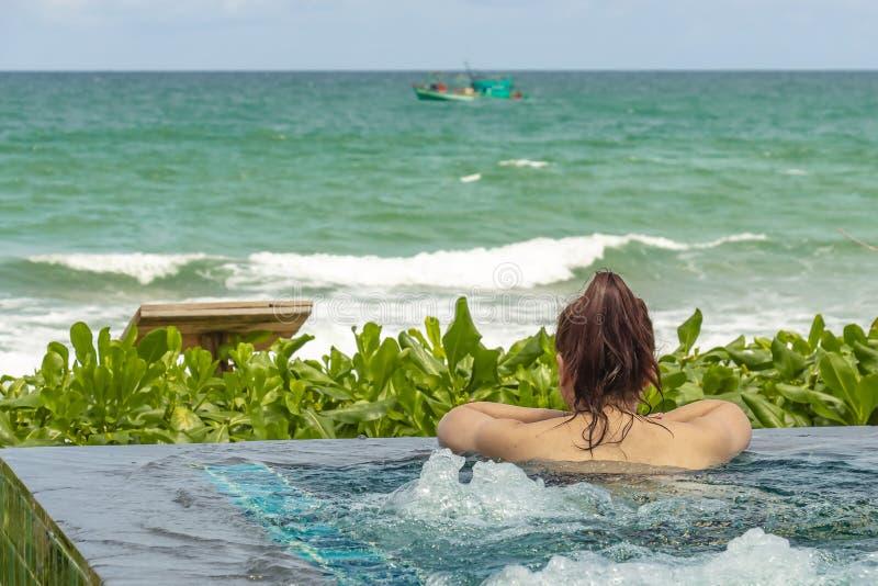 Fêmea em uma piscina da estância de verão que olha para o mar aberto foto de stock