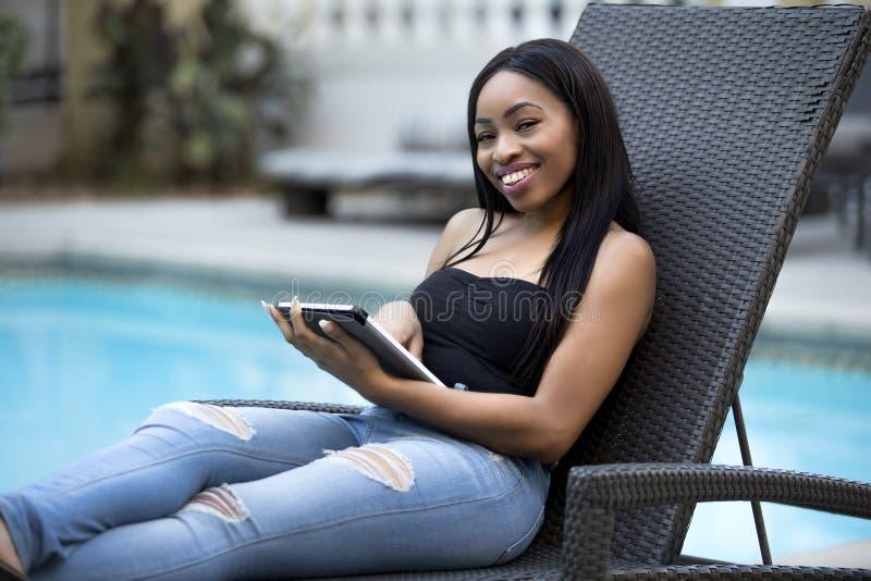 Fêmea em umas férias que fica conectada ao negócio com uma tabuleta foto de stock royalty free