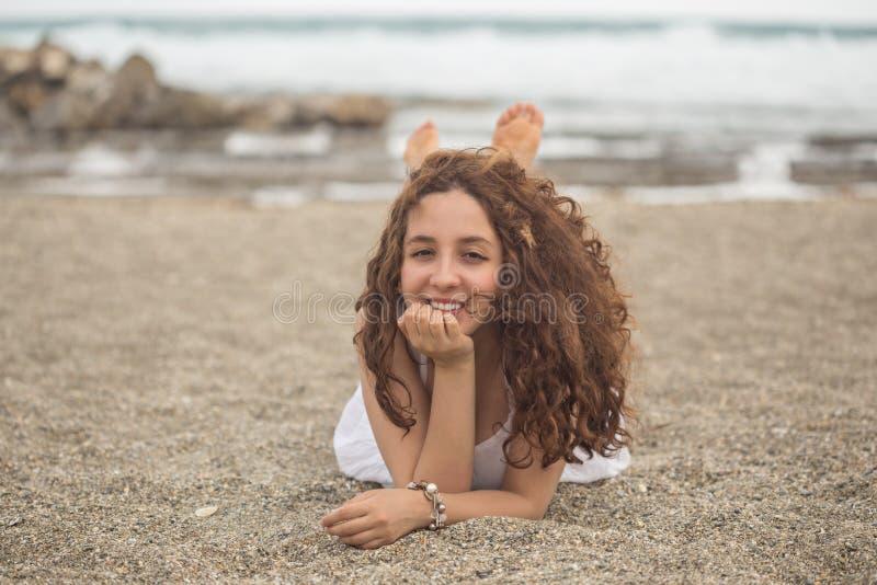 Fêmea encaracolado nova na praia imagem de stock