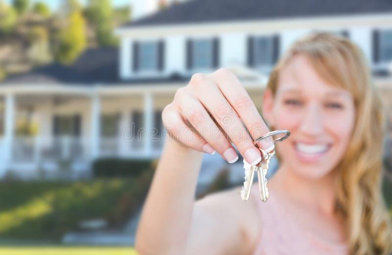 Fêmea entusiasmado nova que guarda chaves da casa na frente da casa nova agradável imagem de stock royalty free