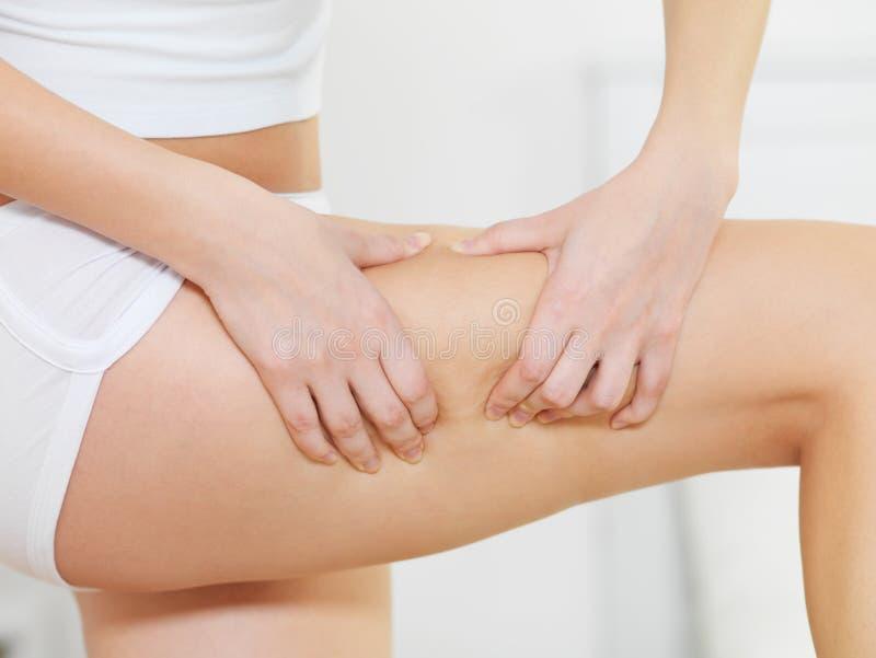 A fêmea espreme a pele do cellulite em seus pés foto de stock