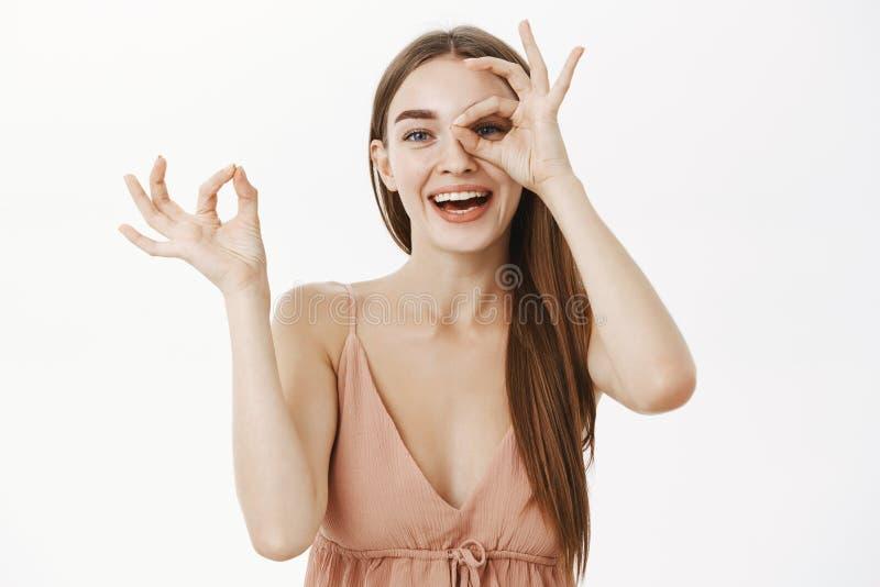 Fêmea europeia delicada brincalhão no vestido na moda bege que faz o gesto aprovado sobre o olho e que faz xixi através do furo n imagem de stock