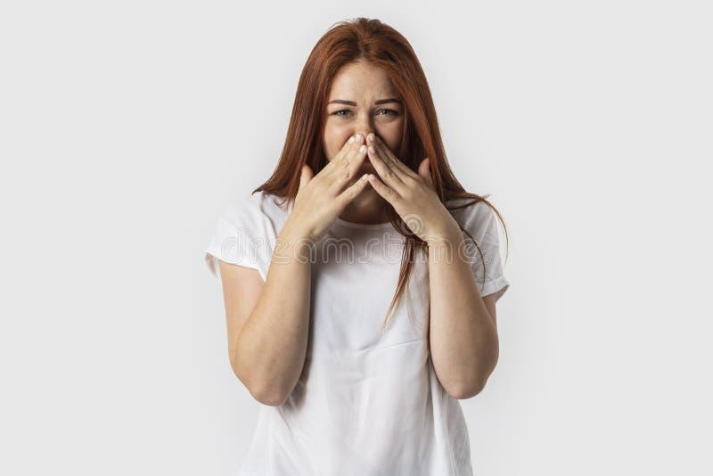 Fêmea europeia do ruivo novo isolada no fundo branco vestido no t-shirt branco, cobrindo o nariz com as mãos que experimentam o f foto de stock