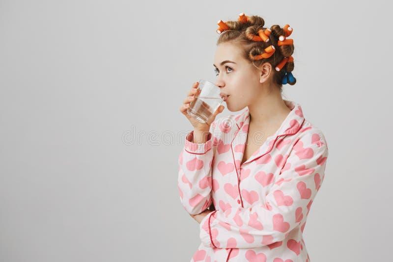A fêmea europeia nova encantador em encrespadores de cabelo e os pyjamas com coração imprimirem, estando metade-girados quando ág fotografia de stock royalty free