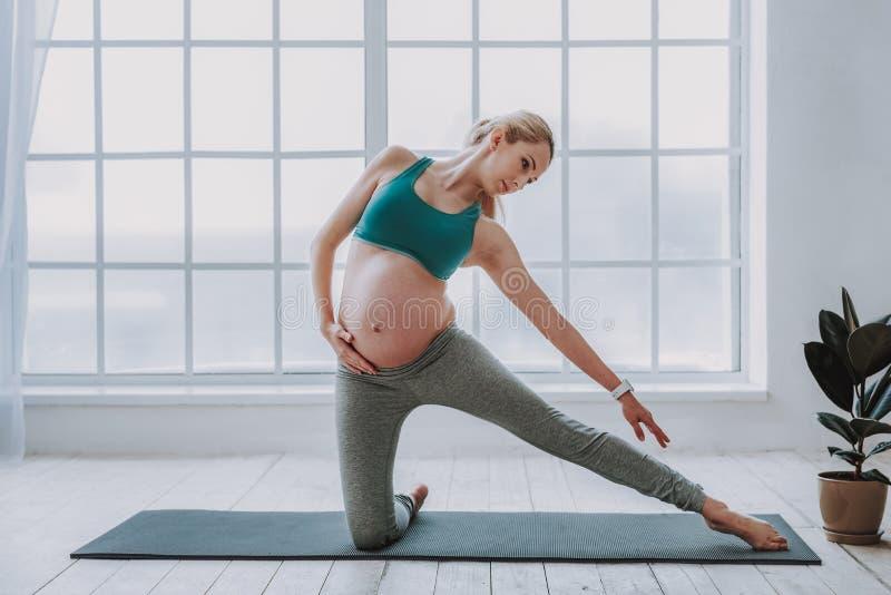 Fêmea expectante bonita na roupa do exercício que faz a ioga fotos de stock