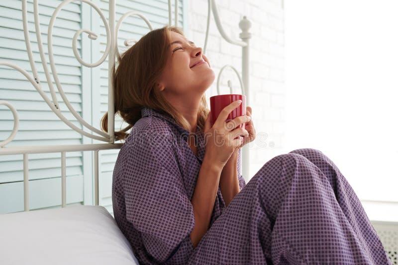 Fêmea feliz atrativa nos pijamas roxos que sentam-se na cabeceira fotografia de stock