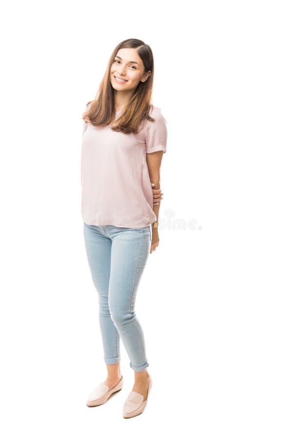 A fêmea feliz com mãos atrás suporta sobre o fundo liso imagem de stock