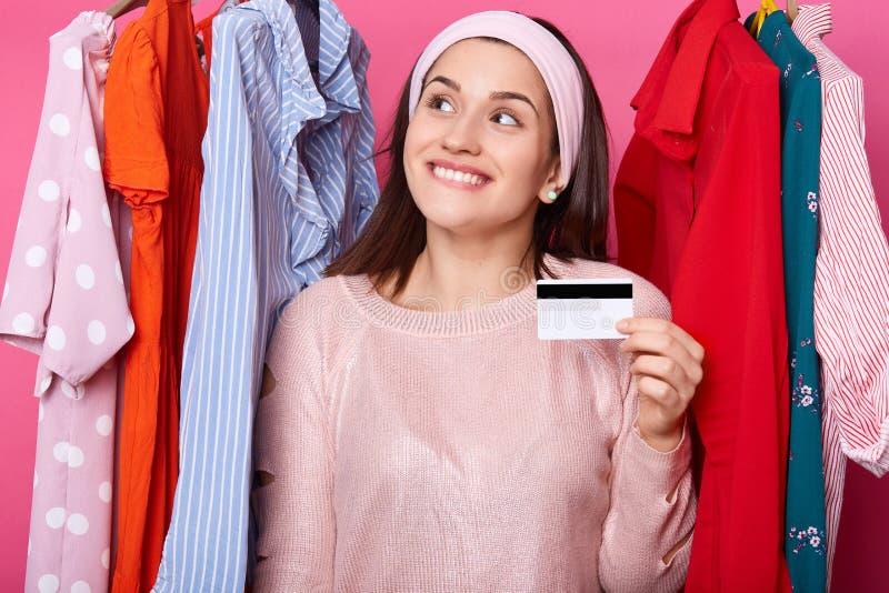 A fêmea feliz guarda um cartão e sorrisos de crédito O cliente novo sente viscosidades, morde seu bordo A mulher atrativa tem car fotos de stock royalty free