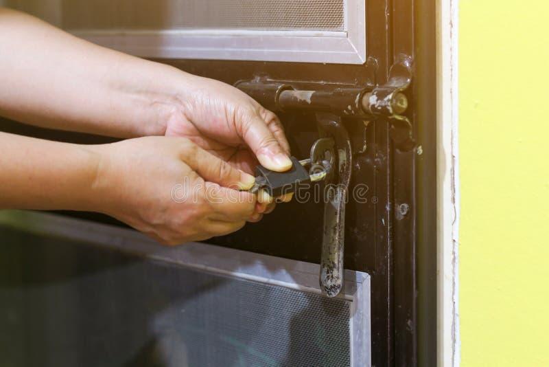 A fêmea gerencie a chave no fechamento na porta exterior aberta, plutônio imagem de stock