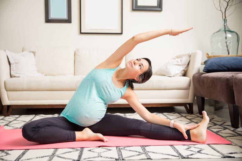 Fêmea grávida com fazer levantado braço esticando o exercício na esteira imagens de stock royalty free