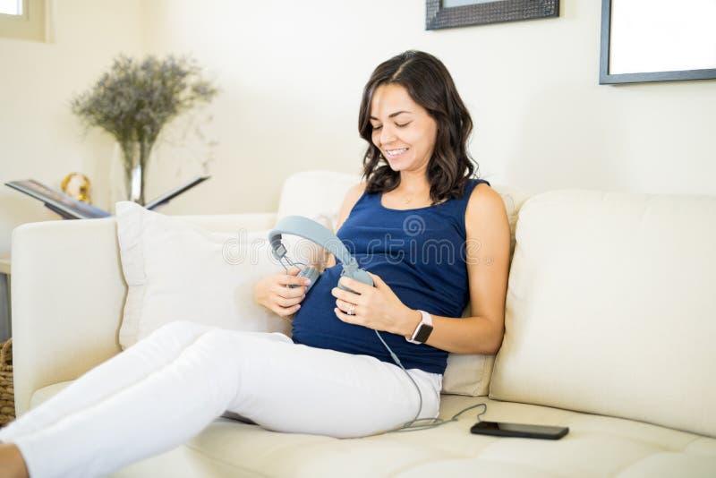 Fêmea grávida com os fones de ouvido na barriga em casa fotos de stock royalty free