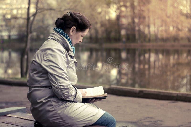 Fêmea idosa na lagoa no parque no livro de leitura do banco fotografia de stock