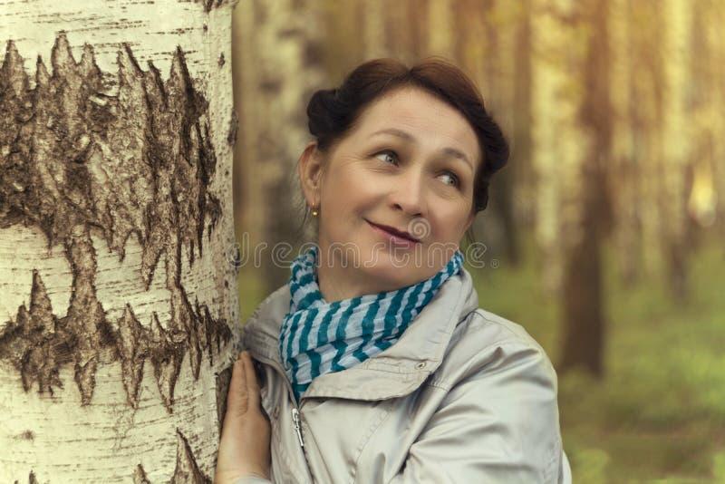 Fêmea idosa no vidoeiro no parque, por do sol fotografia de stock royalty free
