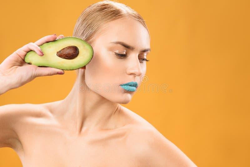 Fêmea loura bonita com abacate fresco foto de stock