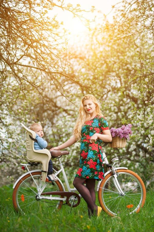 Fêmea loura com a bicicleta da cidade com o bebê na cadeira da bicicleta imagem de stock royalty free
