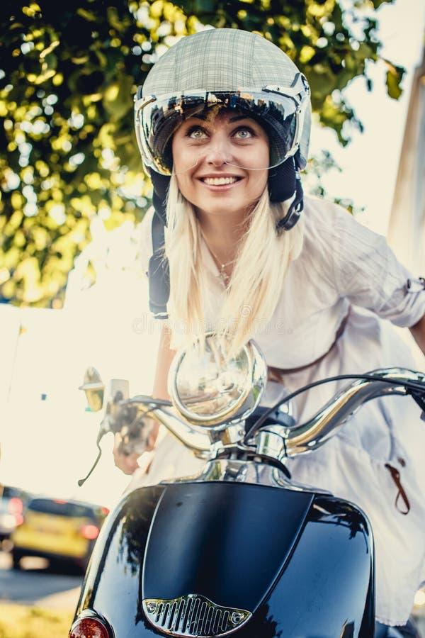 Fêmea loura de sorriso no capacete do moto imagens de stock royalty free