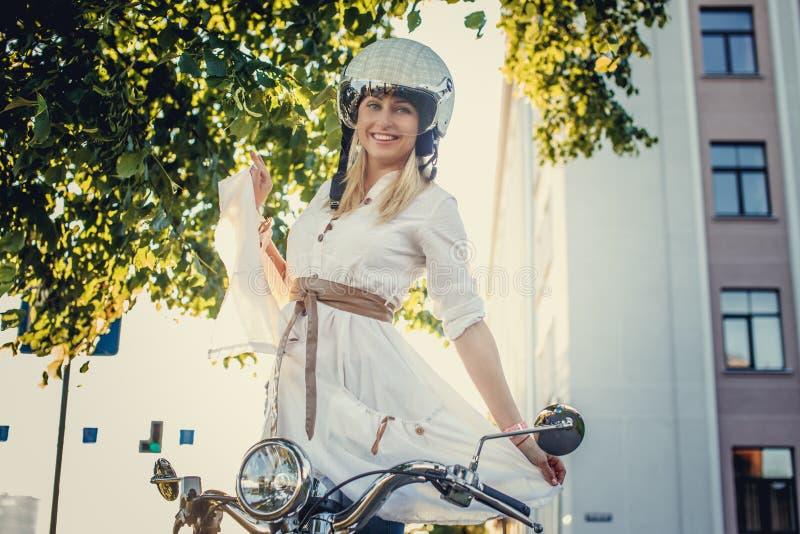 Fêmea loura de sorriso no capacete do moto imagem de stock