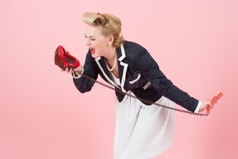 A fêmea loura fala emocionalmente sobre o telefone Senhora que grita no telefone vermelho dos bordos Bordos à conversação dos bor foto de stock royalty free