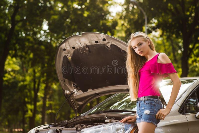 Fêmea loura nova atrativa com carro quebrado fotos de stock