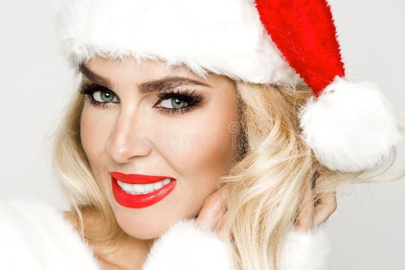 Fêmea loura 'sexy', sorrindo bonita vestida em um chapéu de Santa Claus Menina sensual da beleza para o Natal fotos de stock