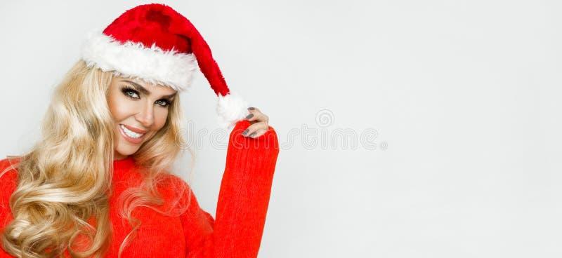 Fêmea loura 'sexy', sorrindo bonita vestida em um chapéu de Santa Claus Menina sensual da beleza para o Natal fotografia de stock