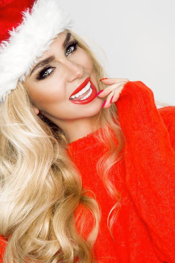 Fêmea loura 'sexy', sorrindo bonita vestida em um chapéu de Santa Claus Menina sensual da beleza para o Natal fotos de stock royalty free