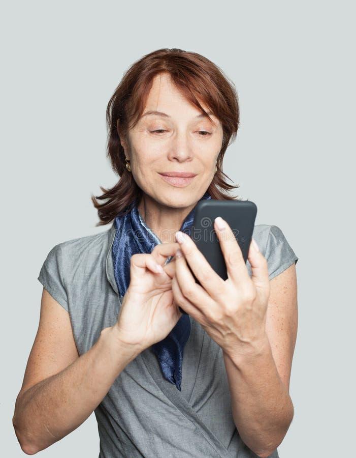 Fêmea madura de sorriso com smartphone fotos de stock