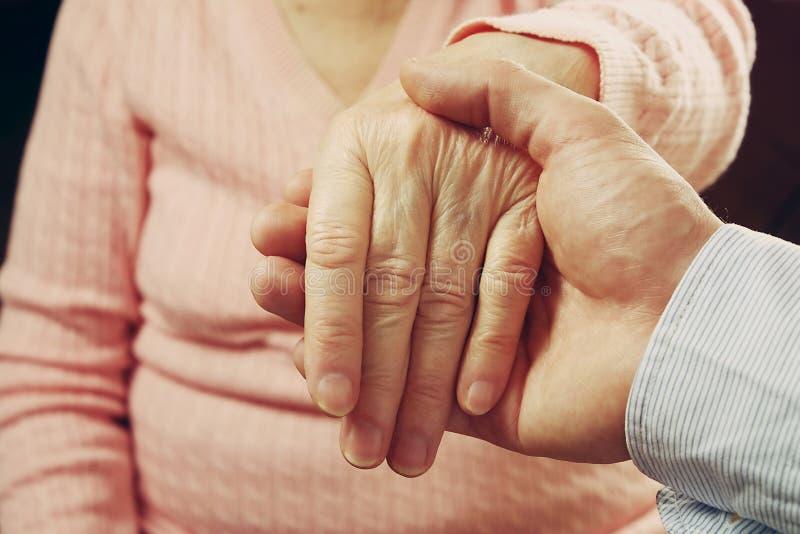 A fêmea madura em instalações de cuidados idosas obtém a ajuda da enfermeira dos pessoais do hospital Feche acima das mãos enruga foto de stock