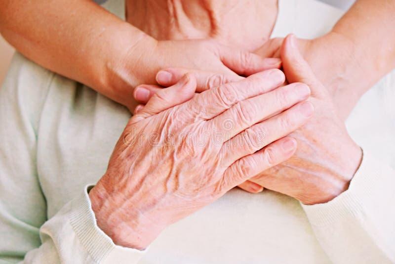 A fêmea madura em instalações de cuidados idosas obtém a ajuda da enfermeira dos pessoais do hospital Feche acima das mãos enruga imagens de stock